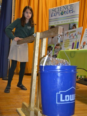 Danielle Palmer, 8, of Vineland, a fourth grader at Edgarton Christian Academy in Newfield demonstrates the use of a lever and the mechanical advantage of its uses during an assembly about a new, after school science club.