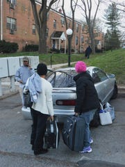 Displaced residents of Evergreen Apartments at Riverfront Heights grab their belongings on Wednesday, March 30, 2016.