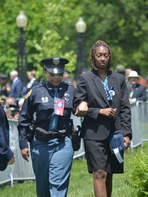 Youlander Ros, whose son, Hattiesburg Police Officer Liquori Tate, was killed by a gunman a year ago, is escorted by Hattiesburg Police Detective Tamera Moore at the National Peace Officers' Memorial Service on Sunday, May 15 .