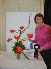 "Diana Reinhardt, Neshanic Garden Club member, with her Division I Design, Section E ""Happily Ever After,"" Class 14 ""Can You Feel the Love Tonight,"" which won the first-place ribbon and the Magical Moments Show Award at the NJ Flower and Garden Show."