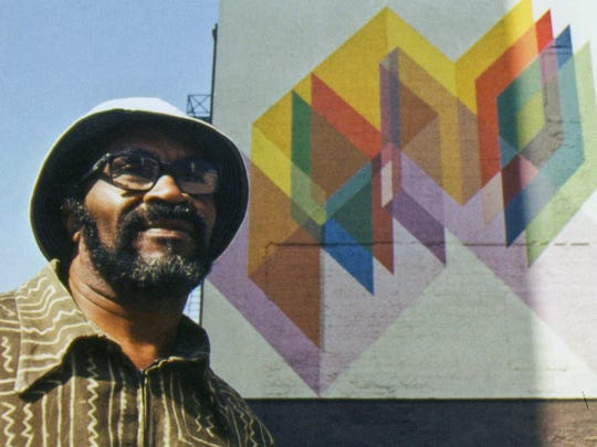 Artist Charles McGee is seen in an undated photo standing under his untitled geometric mural finished in 1974 located at 234 West Larned at Washington Street in Detroit.
