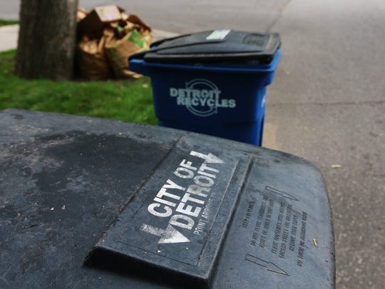 Trash cans line the street for pick-up along Warrington