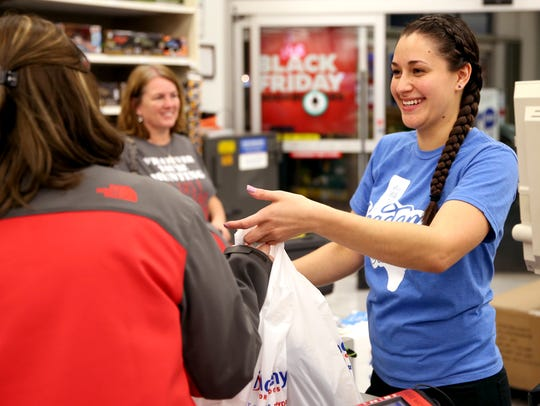 Cashiers at Academy Sports and Outdoors ring up items