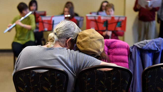 Gregg Viall, from Oshkosh, cuddles with his wife Vivian, who has Alzheimer's disease, while singing holiday songs during the Brown County Memory Cafe at the Green Bay Botanical Garden on Thursday.