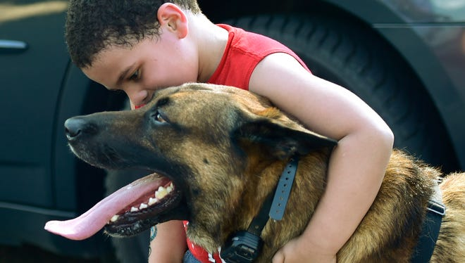 Jose Landro greets police K-9 Rownan. Chambersburg's National Night Out event was held Tuesday, August 2, 2016 at Franklin County's Housing Authority's Meadow Creek Development. The event featured music, face painting, food and bounce houses. During the annual event, first responders got a chance to interact with members of the community.