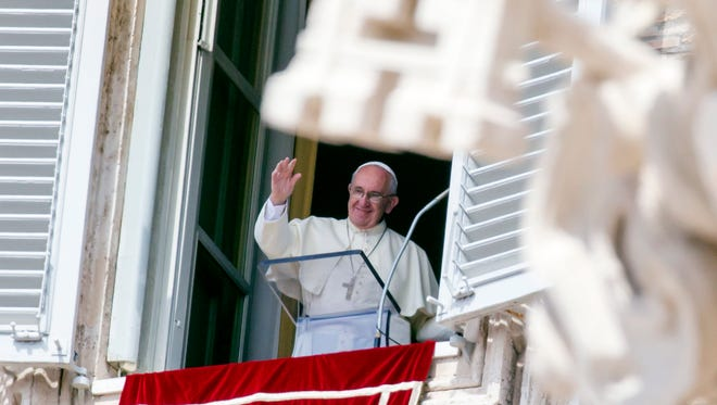 Pope Francis waves to the faithful as he arrives to recite the Angelus noon prayer from his studio window overlooking St. Peter's Square at the Vatican on Sept. 6, 2015.