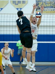 Penfield's Drew Stoler blocks an attack from McQuaid's Brady Darby in the third set at Webster Schroeder High School.