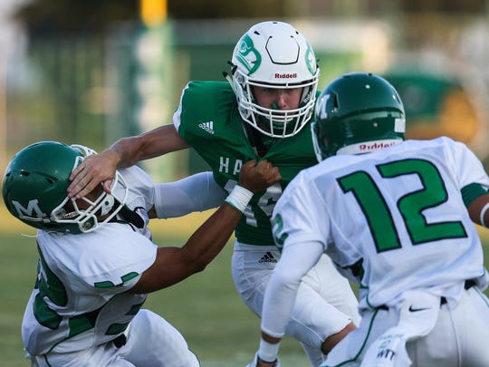 Wall quarterback Brock Rosenquist tries to make his way around Monahans defenders Friday, Sept. 1, 2017, at Hawk Stadium in Wall.