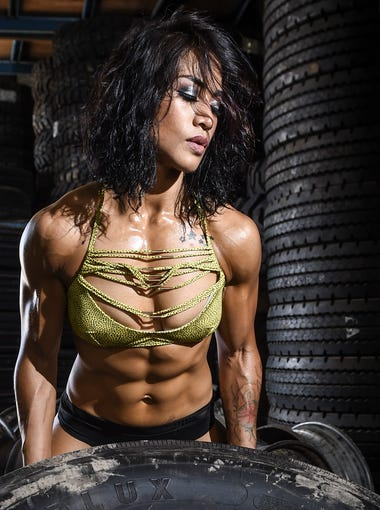 """Desiree Eay of Tamuning makes light work of a truck tire at Triple J Tire on Nov. 11, ten days before competing in the NPC National Bodybuilding Championships in Florida. """"The most beautiful and powerful thing you can ever own is self-confidence,"""" said Eay."""