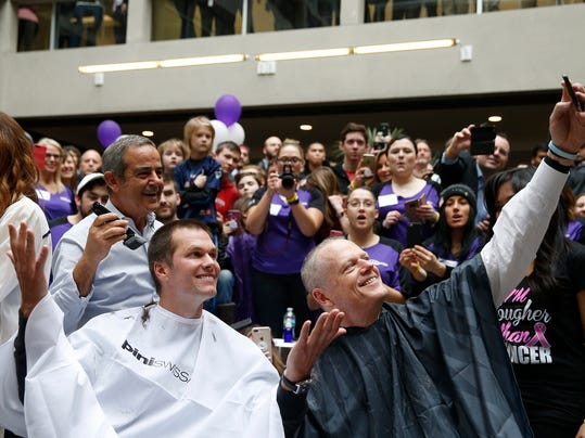 """New England Patriots quarterback Tom Brady, left, and Massachusetts Gov. Charlie Baker, right, pose for a selfie as they get their heads shaved as part of Saving By Shaving 5, Thursday, March 8, 2018, in Quincy, Mass. Brady was the mystery guest at Thursday's """"Saving by Shaving"""" annual fundraiser for the Dana-Farber Cancer Institute in Boston. (Jessica Rinaldi /The Boston Globe via AP)"""