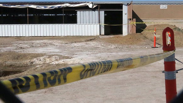 Yellow caution tape surrounds an entrance to a horse
