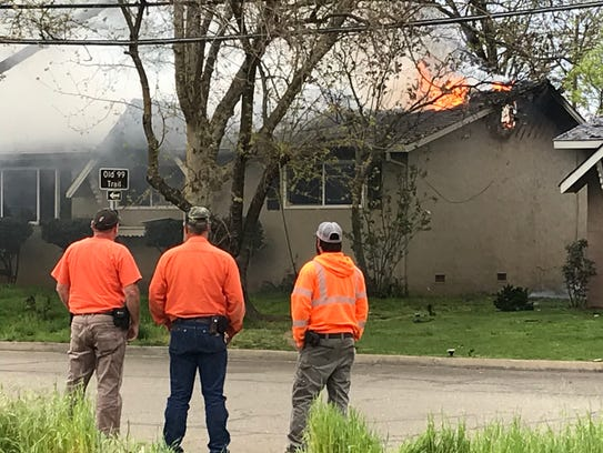 Utility workers watch as a fire burns a home on Bruce