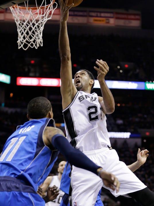 San Antonio Spurs' Tim Duncan (21) shoots over Dallas Mavericks' Monta Ellis (11) during the first quarter of Game 1 of the opening-round NBA basketball playoff series on Sunday, April 20, 2014, in San Antonio. (AP Photo/Eric Gay)