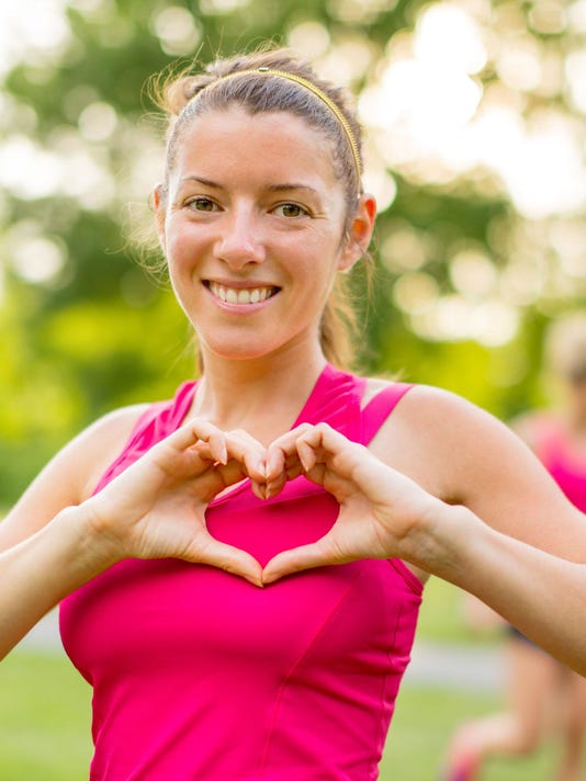 Portrait of an active woman making a heart sign