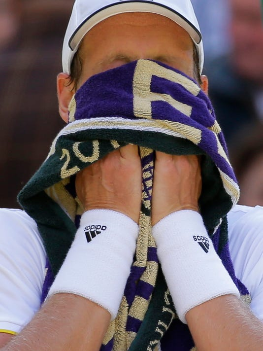 Czech Republic's Tomas Berdych wipes his face during a break as he plays his Men's Singles semifinal match against Switzerland's Roger Federer on day eleven at the Wimbledon Tennis Championships in London, Friday, July 14, 2017. (AP Photo/Alastair Grant)