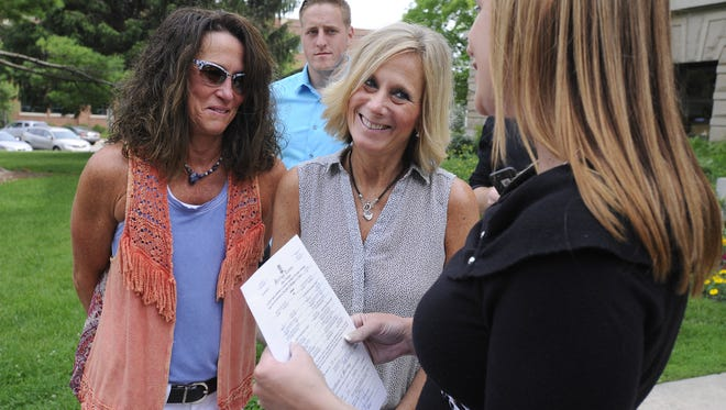 Newly married couple Dawn Chapel, left,  and Lee Chaney, center, talk with Ingham County Clerk Barb Byrum, right, in Mason June 26 after they were married together by Byrum soon after the US Supreme Court ruling striking down Michigan's ban on same-sex marriage. Behind is Lee Chaney's son Lucas Rudd.