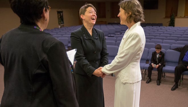 Vivian Wyatt (left), oversees the Indiana marriage of Dawn (in black) and Charlotte Egler on Oct. 10, 2014. The Eglers, who had a holy union ceremony in 1997 at their Indianapolis church and also were married in Canada in 2003, finally legally tied the knot in their home state of Indiana.