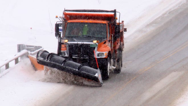 A Vermont Agency of Transportation snow plow crosses a bridge in West Enosburg in 2013.
