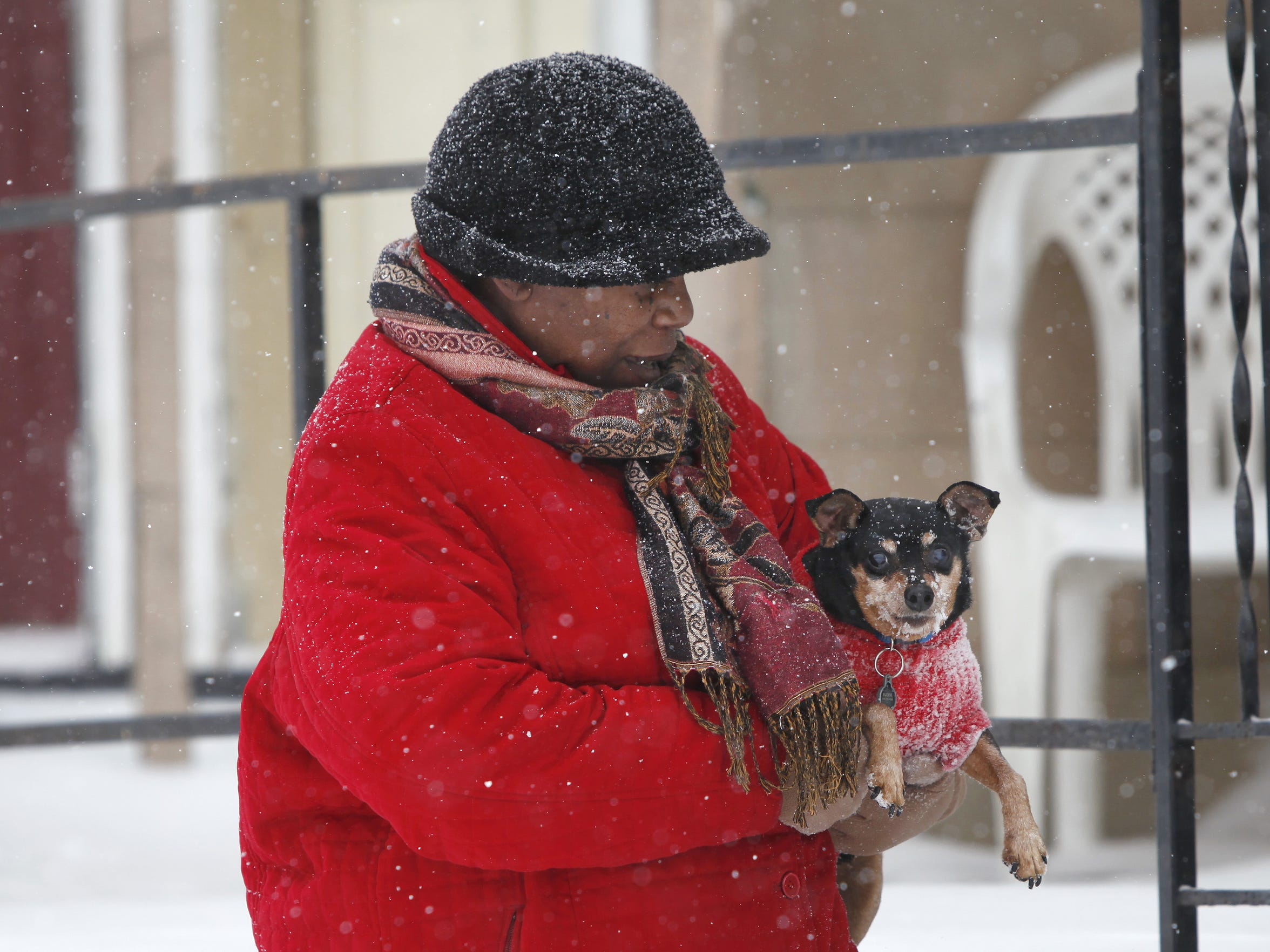 Sheila Evans carries her dog, Buddie,  in from the cold during the Feb. 2 snowstorm.