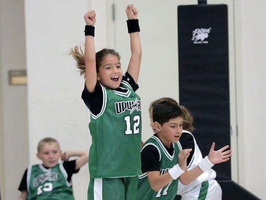 Quincy Hughes, center, celebrates a basket with teammate Kaleb Guerrero during a game in the Upward Sports Program basketball league.