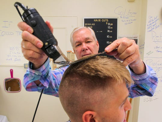 Joe Tankersley, top, gives freshman Air Force ROTC cadet Jacob Sievert, a free haircut on Thursday, on one of the last days the barbershop at The Clemson House will be open. The Clemson House is budgeted for demolition in the future.