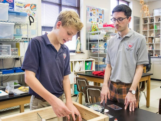 Eighth grader Luke Benzinger discusses how he is using protractors and rulers to solve the optics problem to teacher Patrick Schmitz at the Sacred Heart Cathedral School  in Pensacola on Thursday, February 15, 2018.  Their team is preparing to compete in the state Science Olympiad next month.