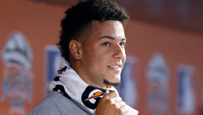 Cincinnati Reds starting pitcher Luis Castillo smiles as he looks out of the dugout during the ninth inning of a baseball game against the Miami Marlins, Sunday, July 30, 2017, in Miami. (AP Photo/Wilfredo Lee)