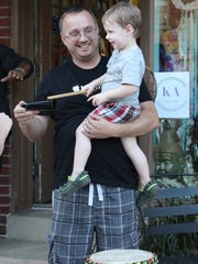 Dennis Citkowicz, 2, plays some instruments as his dad, Rich, holds him.