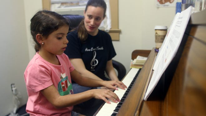 Isabella Mercado, age 7 of  Milltown plays piano under the supervision of instructor Jenna D'Onofrio, Thursday, September 10, 2015, at the North Brunswick School of Music in Milltown, NJ.