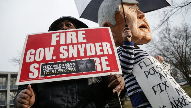 Colleen Liggins of Flint stands with a sign for the firing of Governor Rick Snyder while protesting with others in front of Flint City Hall on Friday, Jan. 8, 2016.