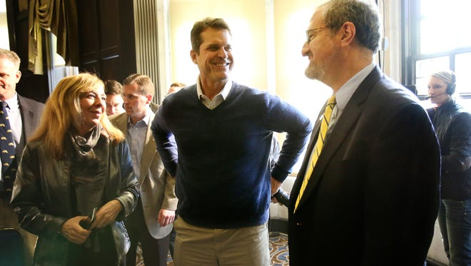 Michigan football coach Jim Harbaugh, center, talks with U-M president Mark Schlissel, right, after a news conference in Ann Arbor on Friday, Jan. 29, 2016.