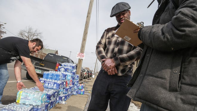 Flint resident Quincy Murphy (center) gathers information from people interested in looking to support a petition to recall Governor Rick Snyder or help and collect signatures as they go to vote during the Michigan Primary election at Berston Field House in Flint on Tuesday March 7, 2016 as a member of the UAW Local 659 of Flint loads donated water they brought to give to Flint residents.