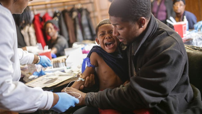 Mike Henry Sr. of Grand Blanc holds his grandson Kaiden Olivares, 3, as he screams while giving a blood sample to be tested for lead on Saturday January 23, 2016 at the Masonic Temple in downtown Flint. 'I'm upset I had to do that to him,' Henry Sr. said who moved with his family outside of the city to Grand Blanc. 'My grandson has had rashes. He's been in the hospital. We have a concern now about the hospital's water. My daughter has hair loss in the past that we've had no clue. We're just trying to find out if maybe that's it. Our whole family resides in Flint. We've ate in Flint. We've drank water in Flint. We've been in Flint restaurants so we have high concern.'