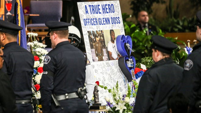 A poster with condolences and photographs sits next to the casket during the funeral for fallen Detroit Police officer Glenn Doss at Greater Grace Temple in Detroit on Friday, Feb. 2, 2018.