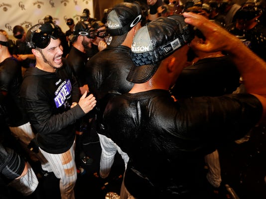 Colorado Rockies third baseman Nolan Arenado, left, celebrates with teammates after securing a National League Wild Card berth after a baseball game Saturday, Sept. 30, 2017, in Denver. The Los Angeles Dodgers defeated the Rockies 5-3. (AP Photo/David Zalubowski)