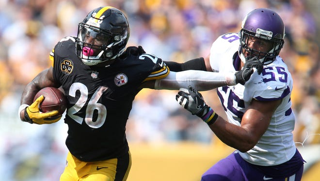 Pittsburgh Steelers running back Le'Veon Bell (26) carries the ball against Minnesota Vikings outside linebacker Anthony Barr (55) during the fourth quarter at Heinz Field. The Steelers won 26-9.