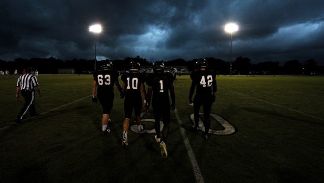 Trinity Christian Academy captains Heath Harris (63), Noah Holsinger (10), Viktor Horton (1) and Zach Yarbrough (42) walk toward midfield for the coin toss versus University School of Jackson at TCA in Jackson, Tenn., on Friday, Aug. 26, 2016. The coin toss was the only thing that counted from Friday night as weather forced kickoff until the next day.
