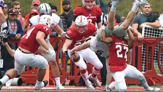 The St. John's University defense tries unsuccessfully to stop a touchdown by University of St. Thomas quarterback Alex Fenske from scoring during the first half Saturday at Clemens Stadium in Collegeville.