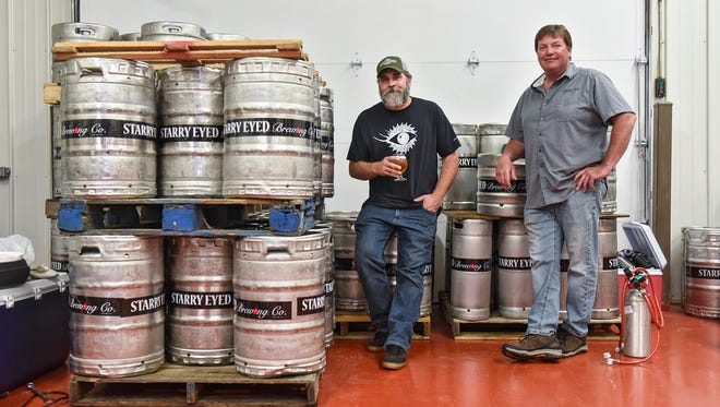 Tom Goebel and Kyle Kieffer stand near kegs filled with fresh Starry Eyed Brewing Co. beer Wednesday, June 6, in Little Falls.