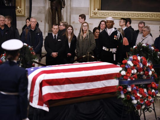 Visitors pay their respects in front of the flag-draped casket of former U.S. President George H.W. Bush at the U.S Capitol Rotunda on Dec. 3, 2018 in Washington, D.C. (Olivier Douliery/Abaca Press/TNS)