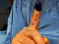 A young woman shows her inked finger after casting her vote at a polling station in Herat, Afghanistan, on April 5.