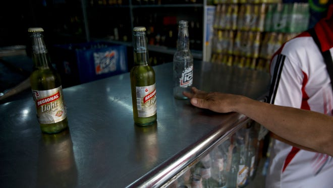 A customer returns an empty Polar beer bottle and buys two others by another maker after Polar beers sold out at the store in Caracas, Venezuela, on July 28, 2015.