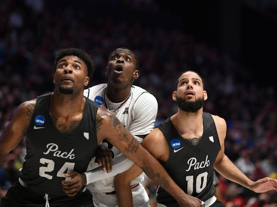 Mar 18, 2018; Nashville, TN, USA; Nevada Wolf Pack guard Jordan Caroline (24), Cincinnati Bearcats forward Tre Scott (13), and Nevada Wolf Pack forward Caleb Martin (10) box out for a rebound during the first half in the second round of the 2018 NCAA Tournament at Bridgestone Arena. Mandatory Credit: Christopher Hanewinckel-USA TODAY Sports