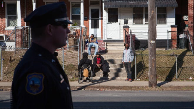 Residents look on as Officer Devon Jones patrols along East 22nd Street in Wilmington as part of Operation Disrupt earlier this year.