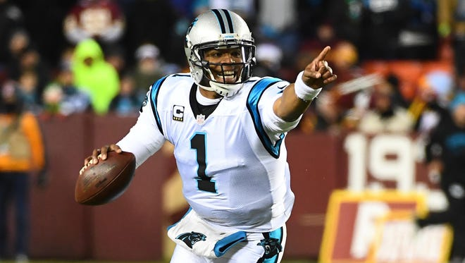 Carolina Panthers quarterback Cam Newton (1) rolls out against the Washington Redskins during the first half at FedEx Field.