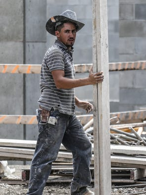 Construction crew member Kevin Arreola carries planks on the job site for  the Pulliam Square project, on the soon-to-be-former Indianapolis Star property, Wednesday, Aug. 27, 2014.