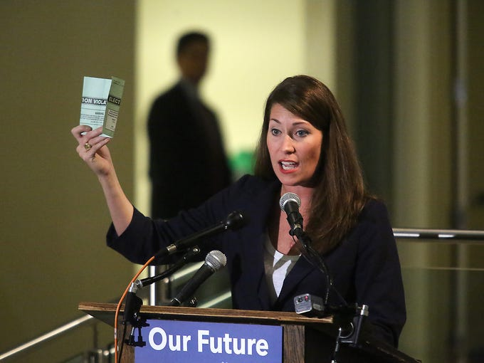 Alison Lundergan Grimes holds up a mailer sent out