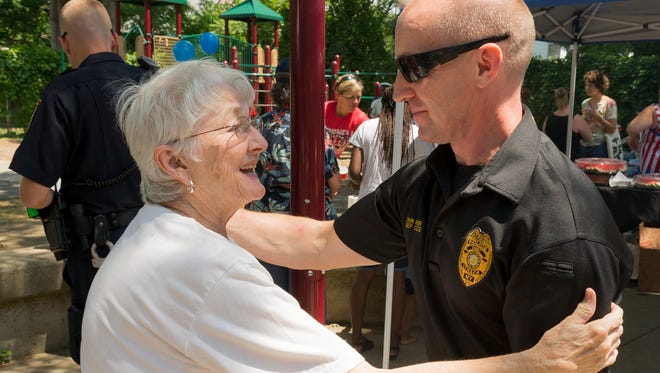Eugenia Landers of Ithaca is greeted by Ithaca Police Chief John Barber, Saturday afternoon at the Second Annual Ithaca Police Department Barbecue.