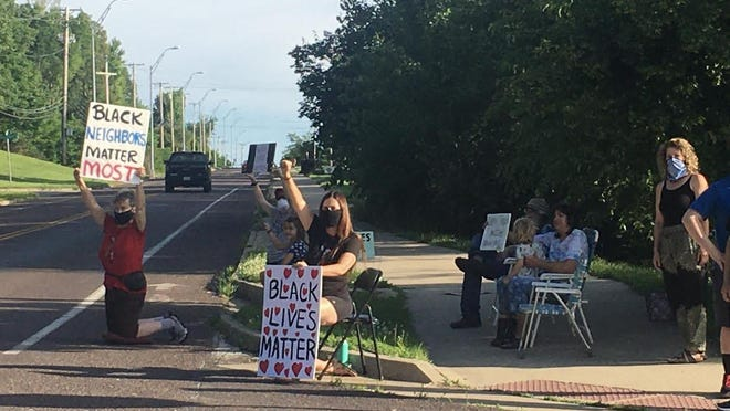 A protest Friday evening at Old Highway 63 and Bluffdale Drive. Suzan Franck is seated in the chair with the Black Lives Matter sign. Sutu Forte is kneeling with the Black Neighbors Matter Most sign.
