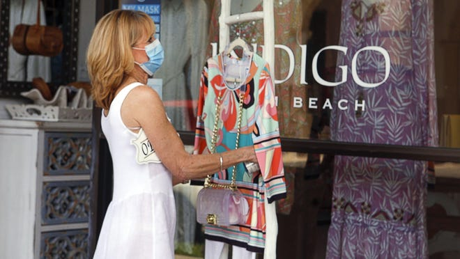 Mimi Simon, manager of Indigo Palm Beach, places an outfit in front of the shop, May 11, 2020. The store reopened Monday after being shut down in response to the coronavirus.